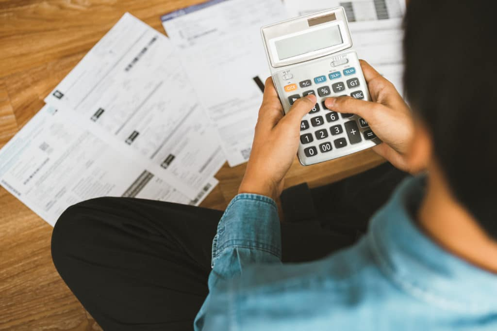 image of man calculating fully loaded employee billable rate per hour